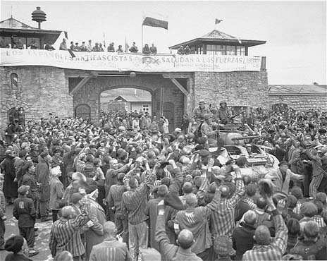 Survivors of Mauthausen cheer American soldiers as they pass through the main gate of the camp. The photograph was taken several days after the liberation of the camp. Mauthausen, Austria, May 9, 1945.