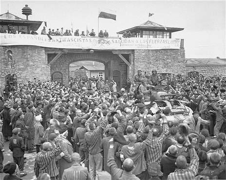 Korban selamat dari Mauthausen mengelu-elukan serdadu Amerika yang melintas melewati gerbang utama kamp. Foto ini diambil beberapa hari setelah pembebasan kamp tersebut. Mauthausen, Austria, 9 Mei 1945.