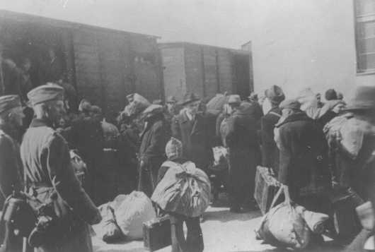 Aleksander Belev, Bulgarian commissioner for Jewish Affairs (center, wearing hat and facing the camera), oversees the deportation of Jews. Skopje, Yugoslavia, March 1943.