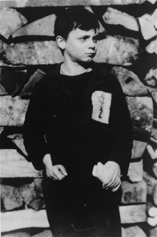 "A Jewish child wears the compulsory Star of David badge with the letter ""Z"" for Zidov, the Croatian word for Jew. Yugoslavia, ca. 1941."