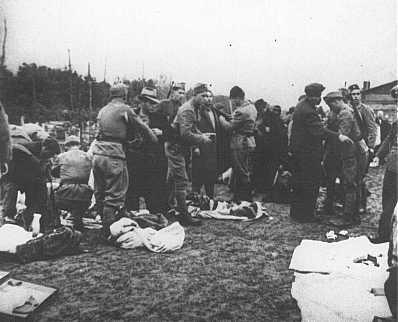 Des gardiens oustachi (fascistes croates) fouillent des prisonniers et leur prennent leurs biens à leur arrivée au camp de concentration de Jasenovac. Yougoslavie, entre 1941 et 1945.