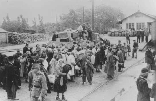 Jewish women, children and the elderly await deportation at the railroad station in Koszeg, a small town in northwestern Hungary. Koszeg, Hungary, 1944.