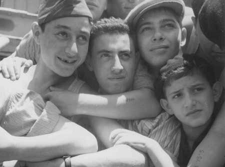 "Youths with camp numbers tattooed on their arms aboard Aliyah Bet (""illegal"" immigration) ship ""Mataroa,"" at the Haifa port. They were denied entry and were deported to Cyprus detention camps. Palestine, July 15, 1945."
