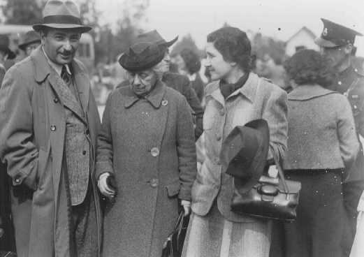 "Eliahu Dobkin of the Jewish Agency (left) and Henrietta Szold, founder of the Hadassah Women's Zionist Organization (second from left), await the arrival of the ""Tehran Children."" Atlit, Palestine, February 18, 1943."