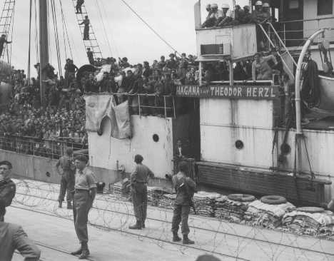 "Refugees on board Aliyah Bet (""illegal"" immigration) ship ""Theodor Herzl"" carry bodies (in white shrouds) of two passengers slain when the ship tried to run a British blockade. Haifa port, Palestine, April 14, 1947."