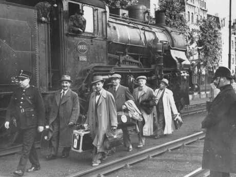 "Belgium agreed to accept some of the Jewish refugee passengers of the ""St. Louis"" after Cuba and the US denied them entry. Here, Belgian police escort some of the passengers after their arrival in Antwerp. Belgium, June 17, 1939."