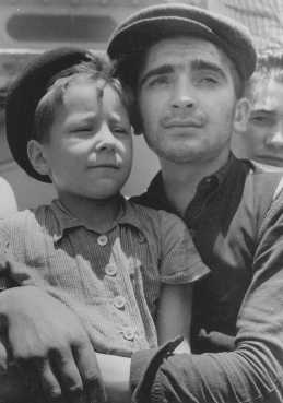 "Eight-year-old Yisrael Meir (Lulek) Lau is held by a fellow  Buchenwald survivor, Elazar Schiff, as they arrive in Palestine aboard the RMS ""Mataroa."" Haifa, Palestine, July 15, 1945."