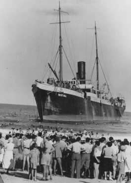 "Aliyah Bet (""illegal"" immigration) ship ""Tiger Hill,"" carrying Jewish refugees from Europe, lands in Tel Aviv, Palestine. Jewish residents of Palestine greet the ship. September 1, 1939."