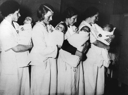 Des mères ayant accouché dans une maternité nationale-socialiste attendent que leurs enfants se fassent examiner par un docteur. Fürstenberg, Allemagne, 28 mars 1937.