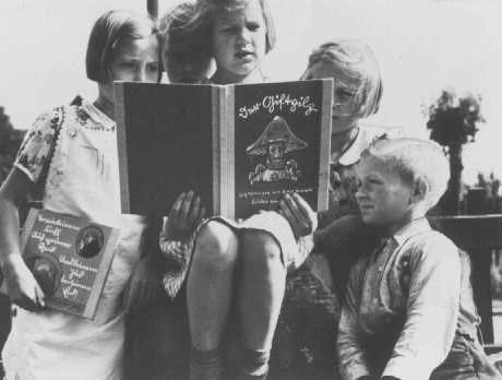 "German children read an anti-Jewish propaganda book titled DER GIFTPILZ ( ""The Poisonous Mushroom""). The girl on the left holds a companion volume, the translated title of which is ""Trust No Fox."" Germany, ca. 1938. (Source record ID: E39 Nr .2381/5)"