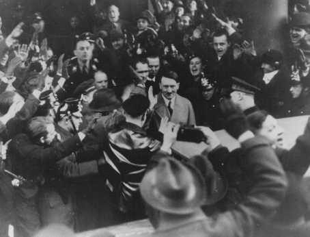 Germans cheer Adolf Hitler as he leaves the Hotel Kaiserhof just after being sworn in as chancellor. Berlin, Germany, January 30, 1933.