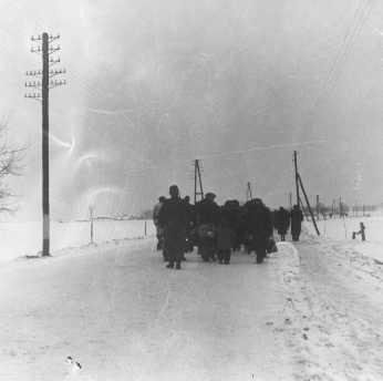A transport of Jewish prisoners marches through the snow from the Bauschovitz train station to Theresienstadt. Czechoslovakia, 1942.
