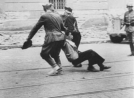 Un soldat allemand observe des civils ukrainiens traînant un Juif le long d'une rue à Lvov. Pologne, juillet 1941.