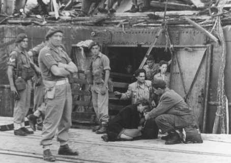 "An exhausted Jewish woman from the ""Exodus 1947"" refugee ship is given a drink as British soldiers stand nearby. The British forcibly returned the passengers to Europe. Haifa, Palestine, July 19, 1947."