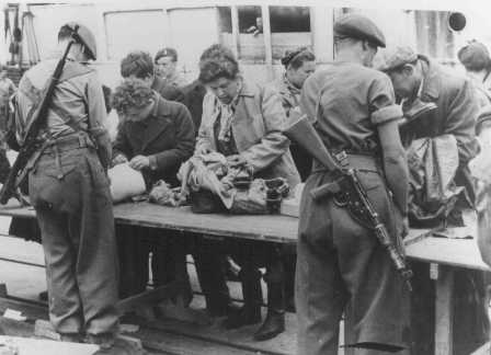 "British soldiers check Jewish refugees from Aliyah Bet (""illegal"" immigration) ship ""Theodor Herzl"" before deporting them to detention camps in Cyprus. Haifa port, Palestine, April 24, 1947."