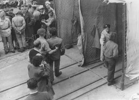 "British soldiers force Jewish refugees from Aliyah Bet (""illegal"" immigration) ship ""Theodor Herzl"" through a disinfection station before deporting them to detention camps in Cyprus. Haifa port, Palestine, April 24, 1947."