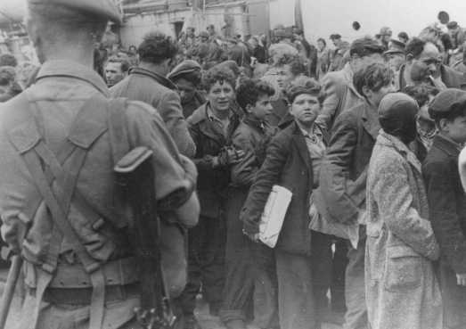 "British soldiers transfer children refugees from the Aliyah Bet (""illegal"" immigration) ship ""Theodor Herzl"" to a vessel for deportation to Cyprus detention camps. Haifa port, Palestine, April 24, 1947."