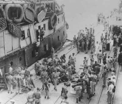 "As UN official Emil Sandstroem (bottom right, white hat) looks on, British soldiers remove Jewish refugees from the ship ""Exodus 1947."" The passengers are deported back to Europe. Haifa, Palestine, July 20, 1947."
