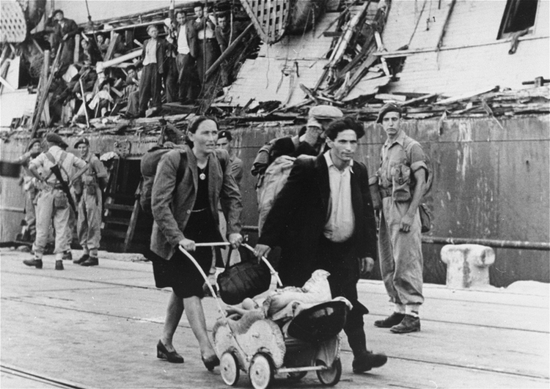 """Refugees removed from the """"Exodus 1947"""" walk to a ship which will return them to Europe. Haifa, Palestine, July 1947."""