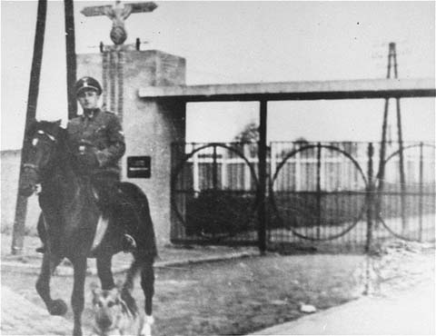 SS Second Lieutenant Gustav Willhaus, camp commandant, rides past the main gate of the Janowska concentration camp. The road from the street and into the camp was paved with tombstones the Nazis removed from Jewish cemeteries. Janowska, Poland, between September 1942 and November 1943.