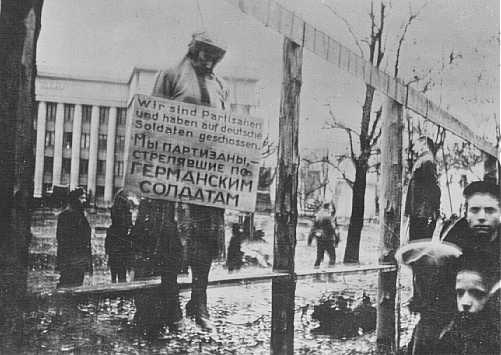 "A hanged Jewish partisan with a sign stating, ""We are partisans and have shot at German soldiers."" Minsk, between 1941 and 1944."