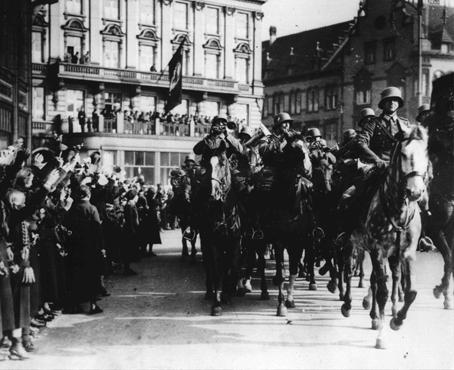 German citizens cheer the entry of German forces into Duesseldorf, on the Rhine, soon after Hitler ordered the entry of German troops into the demilitarized Rhineland, a blatant violation of the Treaty of Versailles. Duesseldorf, Germany, March 8, 1936.