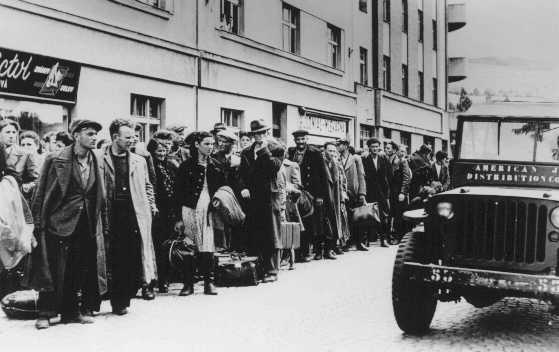 Jewish refugees who fled Poland as part of the postwar mass flight of Jews from eastern Europe (the Brihah) line the streets outside a reception center. Nachod, Czechoslovakia, July 1946.