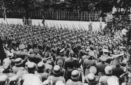 Adolf Hitler (lower right) gives Nazi salute as he reviews victorious German troops. Warsaw, Poland, October 5, 1939.