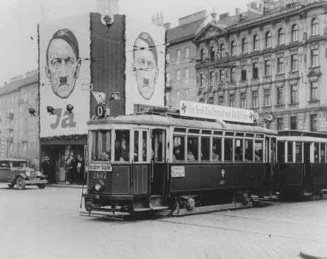 """Un tranvía decorado con esvásticas pasa junto a unas vallas en las que se exhibe el rostro de Hitler. Las vallas exhortan a los austríacos a votar """"Ja"""" (Sí) en el próximo plebiscito sobre la anexión alemana de Austria. Viena, Austria, abril de 1938."""