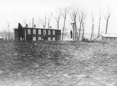In the Kovno ghetto, the body of a Jewish man executed on German orders hangs from gallows erected near the Jewish council building. Kovno, Lithuania, November 18, 1942.