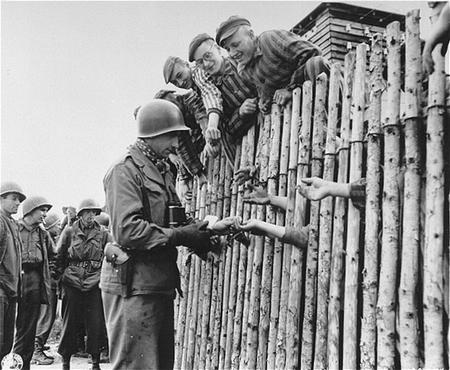 Un soldat américain offre des cigarettes à des détenus du camp de concentration de Dachau fraîchement libérés. Allemagne, 30 avril 1945.