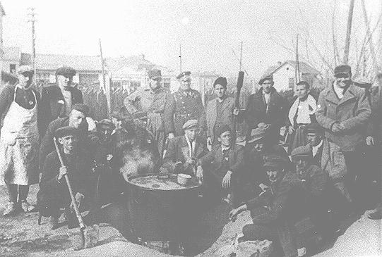 """Jews prepare soup outside the """"Monopol"""" tobacco factory, used as a transit camp by Bulgarian authorities during deportations of Jews from Macedonia. Skopje, Yugoslavia, March 1943."""