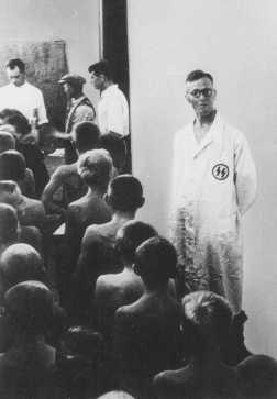 """Des médecins SS examinent des enfants polonais jugés """"racialement valables"""" pour l'adoption par les Allemands. Pologne, octobre 1942."""