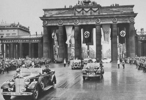 Adolf Hitler attraversa la Porta di Brandeburgo per recasri alla cerimoia di apertura dei Giochi Olimpici. Berlino, Germania, primo agosto 1936.
