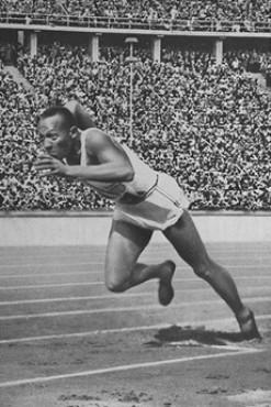 El corredor estadounidense Jesse Owens inicia la carrera de 200 metros en la que estableció una nueva marca olímpica, al cruzar la meta en un tiempo de 20,7 segundos. Berlín, Alemania, 2 de agosto de 1936.