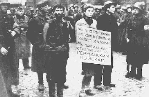 "German soldiers parade three young people through Minsk before their execution. The placard reads: ""We are partisans who shot at Germans soldiers."" Minsk, Soviet Union, October 26, 1941."