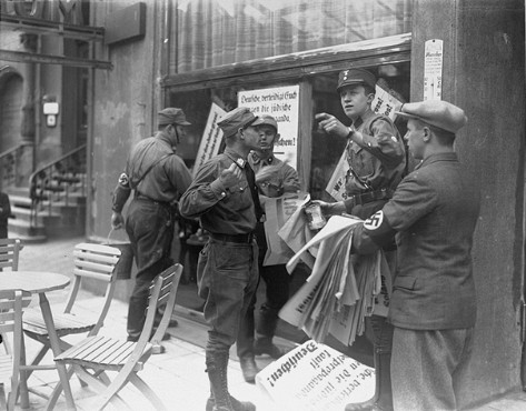 "An SA member instructs others where to post anti-Jewish boycott signs on a commercial street in Germany.  A German civilian wearing a Nazi armband holds a sheaf of anti-Jewish boycott signs, while SA members paste them on a Jewish-owned business. Most of the signs read, ""Germans defend yourselves against Jewish atrocity propaganda/Buy only at German stores.""  Germany, ca. April 1, 1933."