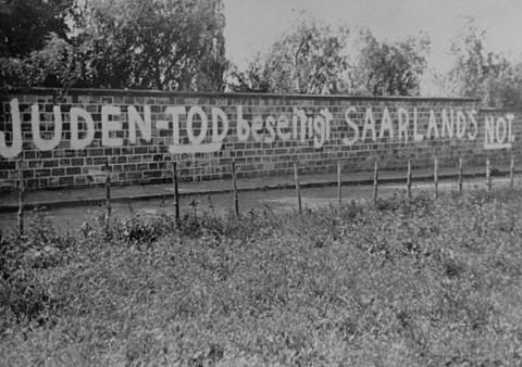 """دیوارنوشته های یهودستیزانه بر دیوار قبرستان يهوديان که از این قرار است: """"با مرگ یهودیان رنج و محنت ایالت زارلانت پایان خواهد یافت."""" برلین، آلمان، نوامبر 1938."""