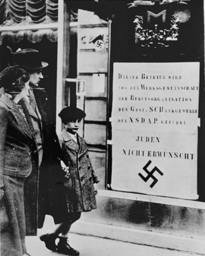 Viennese pedestrians view a large Nazi sign posted on a restaurant window informing the public that this business is run by an organization of the Nazi party and that Jews are not welcome. Vienna, Austria, March-April 1938.