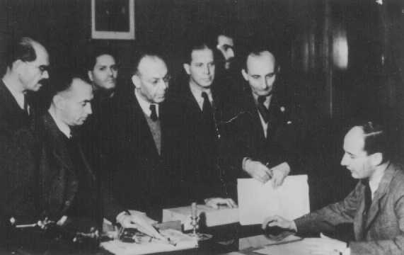 Raoul Wallenberg (seated) at the Swedish legation, with his Hungarian Jewish co-workers. Wallenberg provided thousands of Hungarian Jews with Swedish protective passes. Budapest, November 1944.