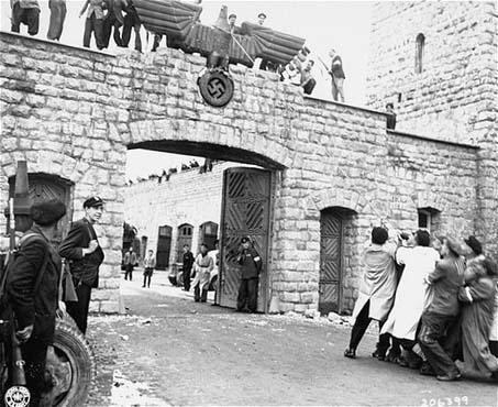 Après la libération du camp de concentration de Mauthausen, des survivants abattent l'aigle nazi au-dessus du portail d'entrée du camp. Mauthausen, Autriche, 6 mai 1945.