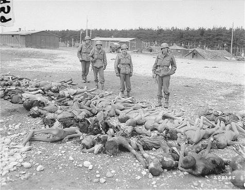Soldados norte-americanos observam corpos de vítimas dos nazistas em Kaufering, parte de uma rede de campos subsidiários do complexo de concentração de Dachau. Landsberg-Kaufering, Alemanha, abril 30, 1945.