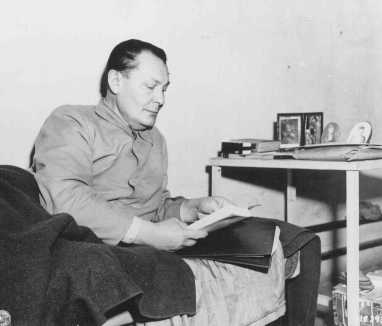 Defendant Herman Goering reads in his prison bunk at Nuremberg. On the table are photographs of his family. December 21, 1945.