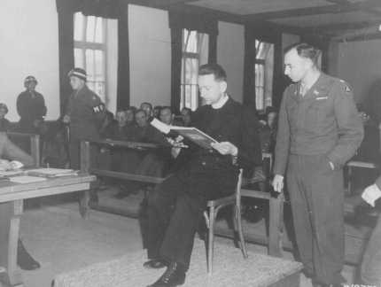 Polish priest Theodore Korcz reads from a medical record presented as evidence at the trial of former personnel from the Dachau concentration camp. The log recorded the deaths of several Catholic priests who were used as subjects in malaria experiments. US Chief Prosecutor Lieutenant Colonel William Denson stands next to him. November 22, 1945.