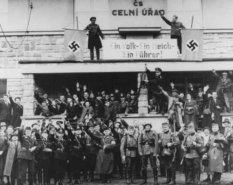 "German troops marching into the Sudetenland stop at a former Czech frontier post. The sign between the swastikas reads: ""One People, One Reich, One Fuehrer."" Grottau, Czechoslovakia, October 2 or 3, 1938."