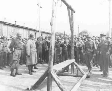 A Dutch survivor of the Ohrdruf camp shows the camp's gallows, which the Germans used to execute prisoners, to US forces (including Generals Eisenhower, Bradley, and Patton). Germany, April 12, 1945.
