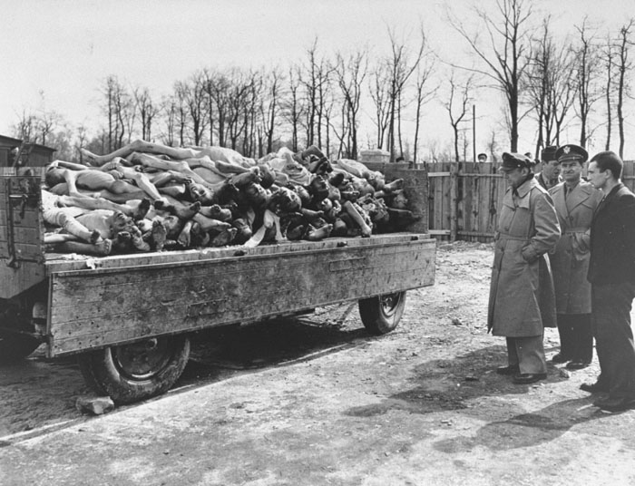 American military personnel view corpses in the Buchenwald concentration camp. This photograph was taken after the liberation of the camp. Germany, April 18, 1945.