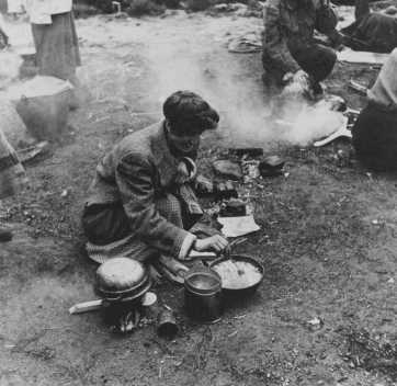 Soon after liberation, camp survivors cook in a field. Bergen-Belsen, Germany, after April 15, 1945.