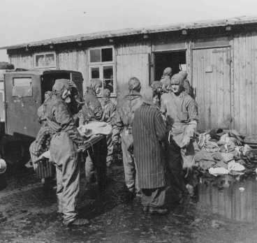 Soon after liberation, British medical officers begin disinfection of camp survivors. Bergen-Belsen, Germany, May 1945.