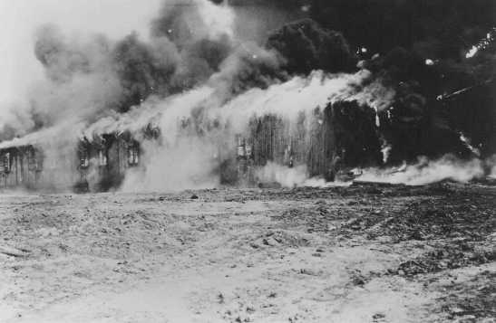 The Bergen-Belsen former concentration camp is burned to the ground to halt the spread of typhus. Germany, May 21, 1945.